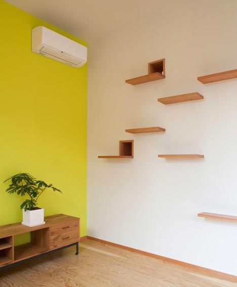 Gato sobre su sistema de escaleras para subir la pared y llegar a otras habitaciones. Está sentado delante de la gatera interior que le da acceso a la biblioteca al otro lado del pared.