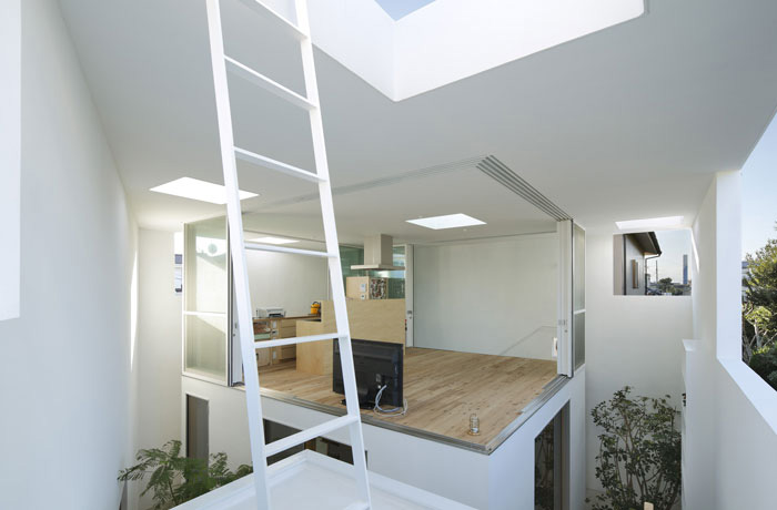 Vista del interior de la casa Inside Out. Se ve el bloque de dormitorio y salón-cocina con los ventanales abiertos. La estructura de la casa es abierta, hay grandes aperturas en las paredes de la casa a la altura del primer piso así pase al aire por las habitaciones.